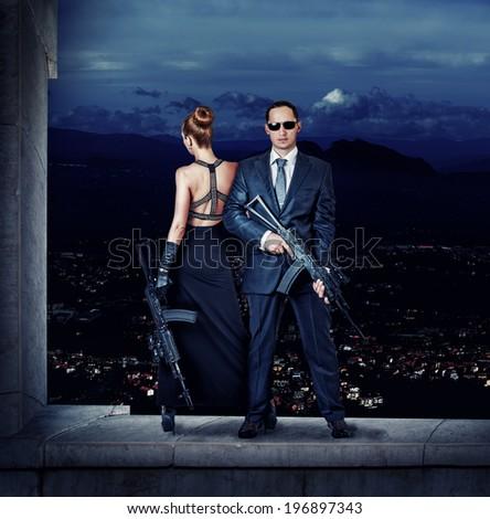Fashionable couple - woman and man holding automatics - stock photo