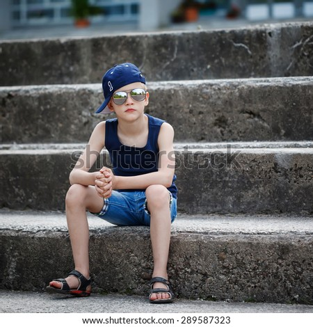 Fashionable little boy in sunglasses and cap siting on stone steps. Childhood.  Summertime. Square. - stock photo