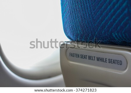 """""""Fasten seat belt while seated"""" to warning passengers on the seat of airplane. - stock photo"""