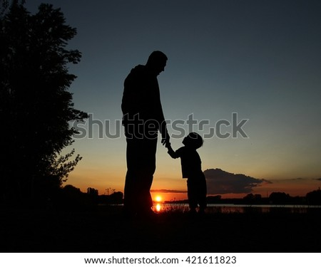 father and son silhouette on sunset - stock photo