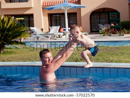 father learning his son to dive into the pool - stock photo