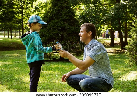 Father with his son in the park .Father is giving water to his boy.  - stock photo