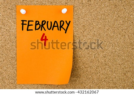 4 FEBRUARY written on orange paper note pinned on cork board with white thumbtacks, copy space available - stock photo