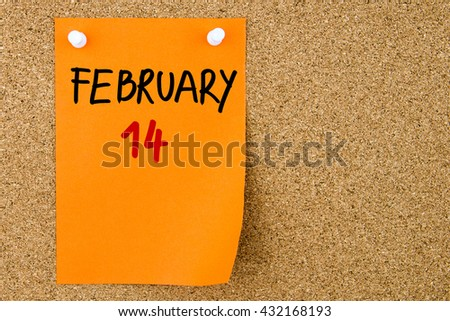 14 FEBRUARY written on orange paper note pinned on cork board with white thumbtacks, copy space available - stock photo