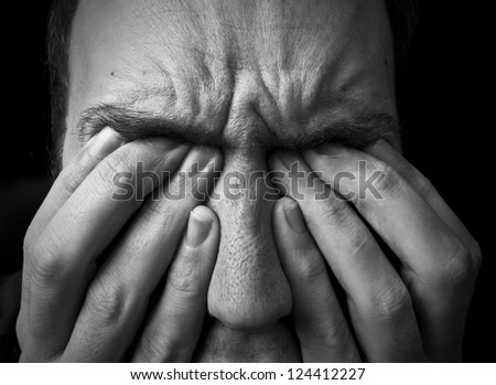 feeling upset / in pain, frowning with fingers covering eyes on black background - stock photo