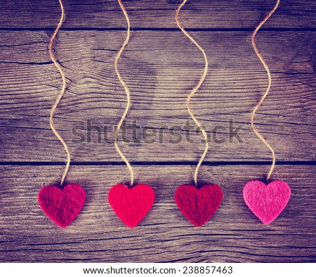 felt fabric love valentine's hearts hanging on rustic driftwood texture background with twine toned with a retro vintage instagram filter effect - stock photo