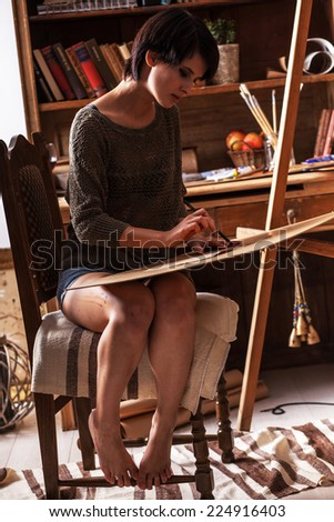 Female artist painter in her studio.Charcoal drawings. - stock photo