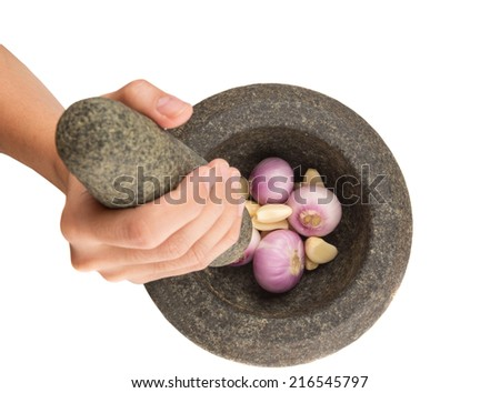 Female hand crunching onions and garlic stone mortar and pestle over white background  - stock photo