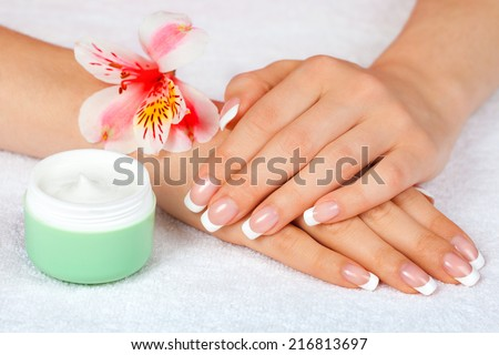Female hands with french manicure near jar of cream on white towel - stock photo