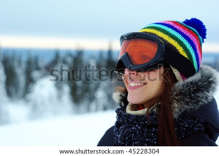 female skier smiling and wearing ski glasses in the mountains - stock photo