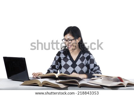 Female student studying at class while typing the source on laptop computer  - stock photo