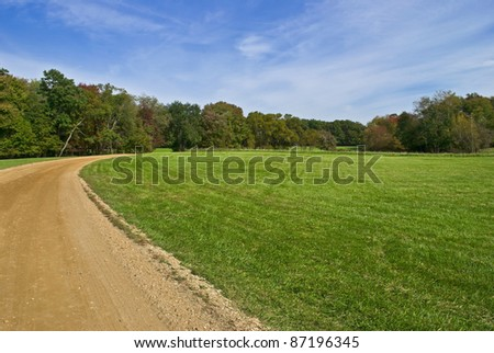 """Field and Trail"" Blue skies, green grass and a dirt road, early Autumn in Central New Jersey. - stock photo"