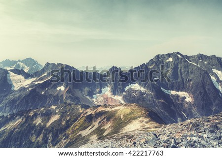 (Film&Instagram Concept): Vintage landscape of Mountains in Northwest America. This vintage landscape has trail, grasses, clouds, mountains, and rocks. This vintage landscape is taken during a day - stock photo