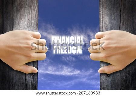 """Financial Freedom"" text in the sky behind 2 hands opening the wooden door. - stock photo"