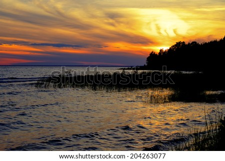 . Fire In The Sky. The sun sets behind a forested peninsula along a remote Lake Michigan coast. Fayette State Park. Garden, Michigan.  - stock photo