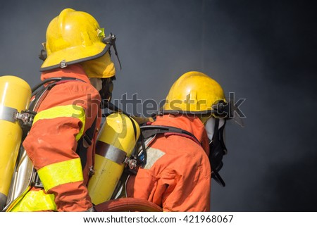 2 firefighters in operation and dark smoke background - stock photo