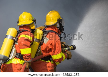 2 firefighters spraying water in fire fighting with dark smoke background - stock photo
