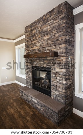 fireplace built with stone and wooden mantel - stock photo
