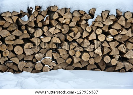 Firewood put in a woodpile brought by snow. Winter in the village. - stock photo