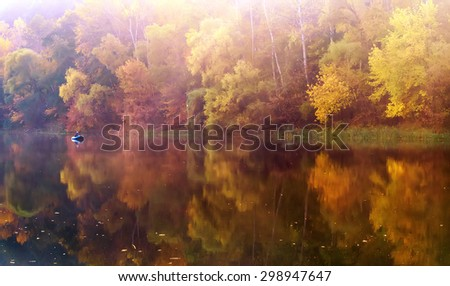 fisherman in the boat on the river. early morning autumn landscape - stock photo