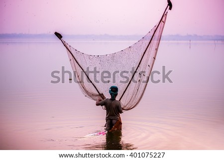 Fishermen fishing by traditional net in the river near U-Bein bridge - stock photo