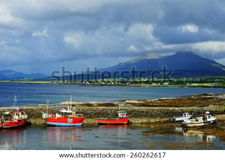 Fishing boats moored at Broadford old Pier and Harbor under a stormy sky, The Isle of Skye, Scotland, United Kingdom - stock photo