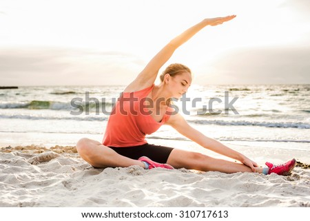Fitness sport model smiling happy doing exercises during outdoor work out on sunrise. Beautiful caucasian female training outside on seaside in the morning - stock photo
