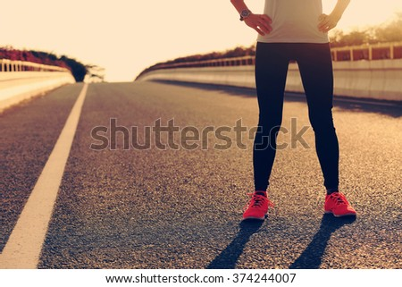 fitness young woman runner standing with her hands on hips on sunrise road - stock photo
