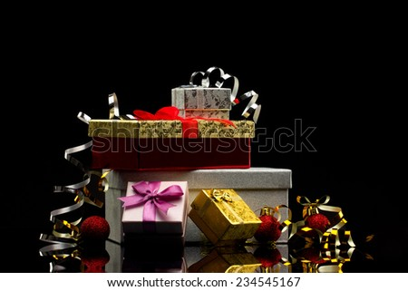 five glamour  gift boxes with bows and  several bright red balls on dark reflection  background - stock photo