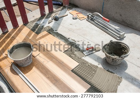 fixing tile with spacers at construction  work - stock photo