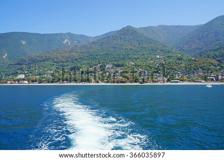 Foamy trace on water behind the boat in the sea against mountains and the city of Gagra in Abkhazia.                               - stock photo