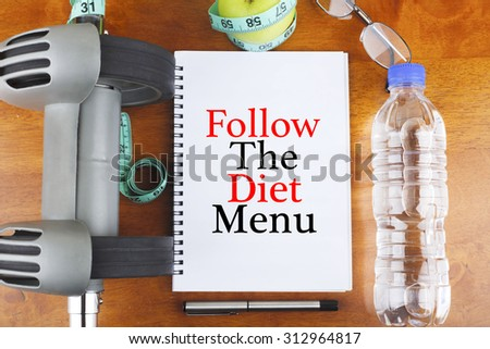 """""""Follow The Diet Menu"""" text on notebook with delicious green apple, measure tape, spectacle, a bottle of mineral water, and bodybuilding tools on wooden background - healthy, exercise and diet concept - stock photo"""