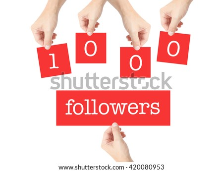 1000 followers written on cards held by hands - stock photo
