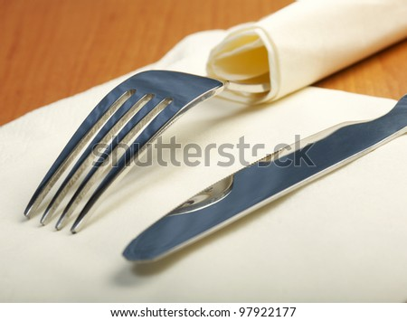 fork and a knife lie on serviette closeup - stock photo