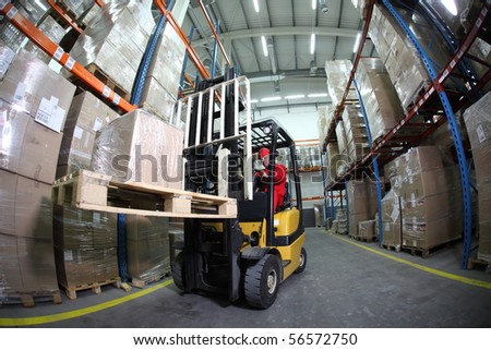 forklift operator at work in warehouse - stock photo