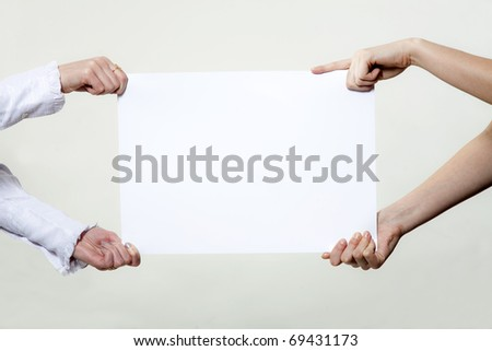 Four hands holding blank advertisement paper - stock photo