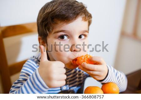 Four years boy eat a mandarin - stock photo