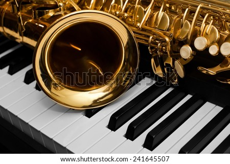 Fragment of the saxophone lying on the piano keys  - stock photo