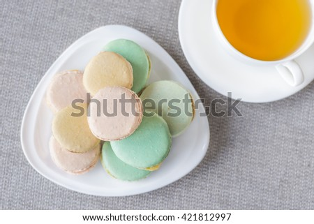 French colorful macaroons sweet dessert and with a cup of tea. - stock photo