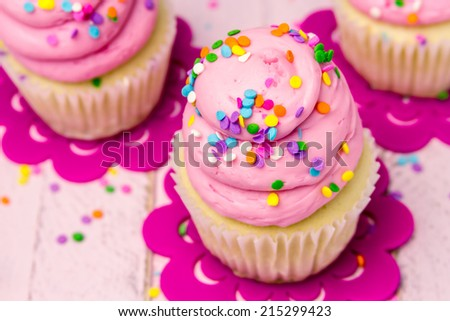 3 fresh baked vanilla cupcakes with pink swirled strawberry frosting topped with colorful sprinkles sitting on flower cut outs - stock photo