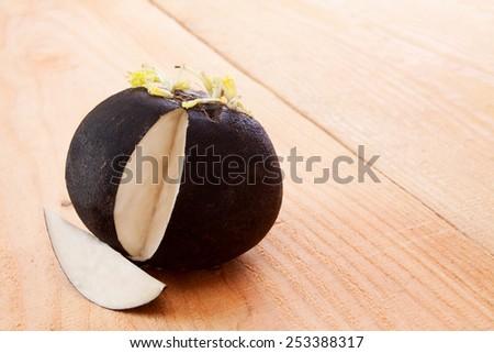 Fresh black  radish isolated on wooden background. - stock photo