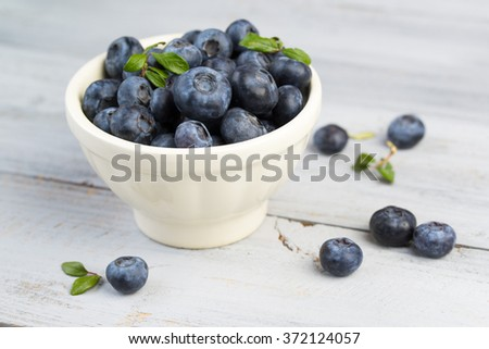 Fresh blueberries in a white bowl on a wooden background - stock photo