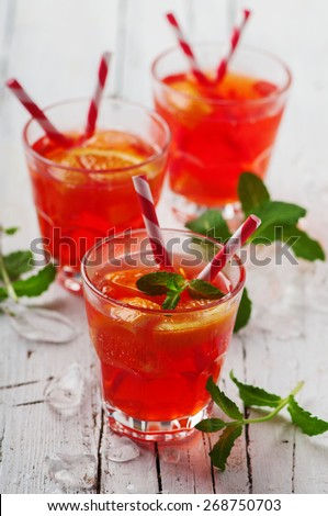 Fresh cocktail with orange, mint and ice, selective focus - stock photo