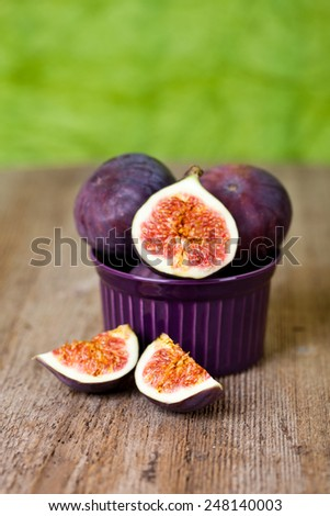 fresh figs in a bowl on rustic wooden table - stock photo