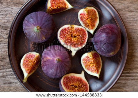fresh figs in a plate on rustic wooden table - stock photo