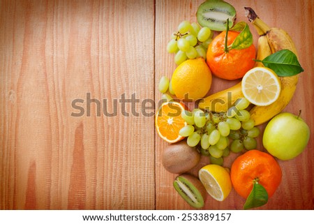 Fresh fruits isolated on wooden background. - stock photo