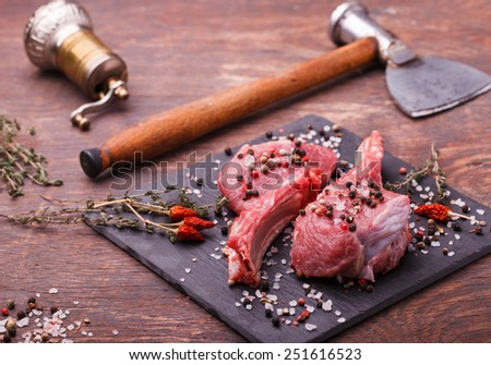 Fresh meat on the bone steak with spices and herbs,on a dark background - stock photo