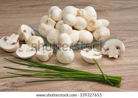 Fresh raw mushrooms with chives - stock photo