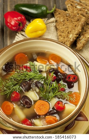 Fresh vegetable soup made of color bean, carrot, potato, red bell pepper, tomato in bowl - stock photo