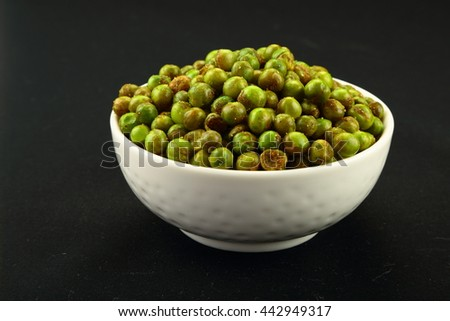 fried green peas {chatpata matar} Indian snack. Dried salted green peas in bowl on white background - stock photo